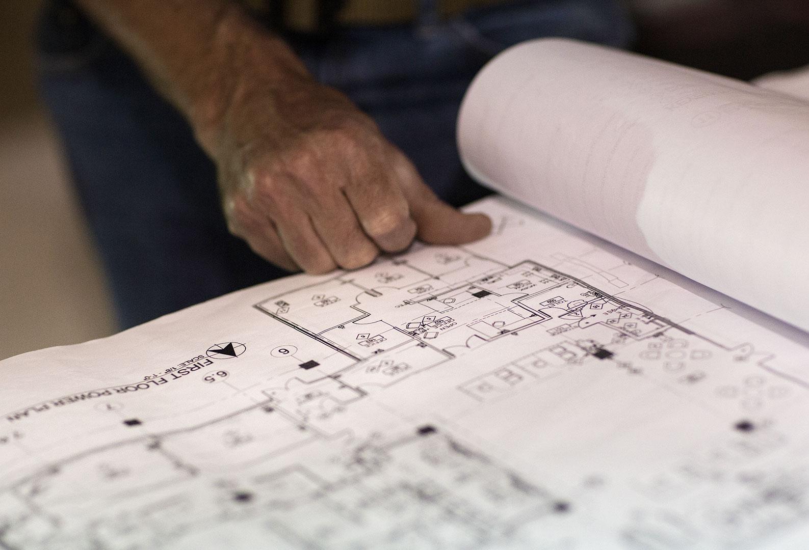 Hand on building blueprint sheet.
